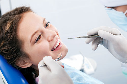 Teenage Girl Smiling While Being Prepped Up for Dental Treatment | Dental Emergencies in Friendly Smiles Center in Mount Laurel, NJ - Dr. Robert Chase