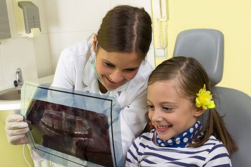 Little Girl with Her Dentist Looking at an X-Ray of the Teeth | Preventative Orthodontics for Kids in Friendly Smiles Center in Mount Laurel, NJ - Dr. Robert Chase